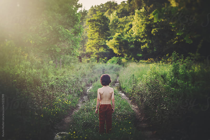 A Young Boy Staring Down a Sunny Path by Kevin Keller for Stocksy United