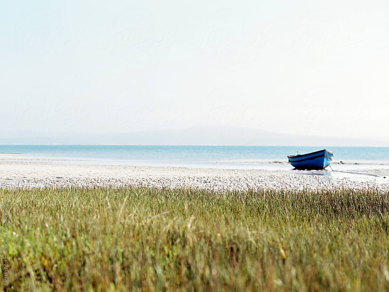 Single boat on a beach in Churchaven, South Africa by Kirstin Mckee for Stocksy United