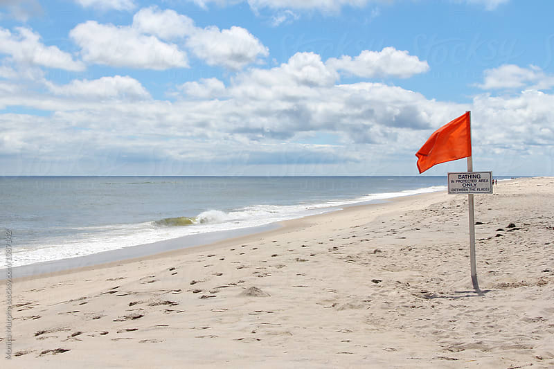 Empty beach on a cloudy day with blue skies by Monica Murphy for Stocksy United