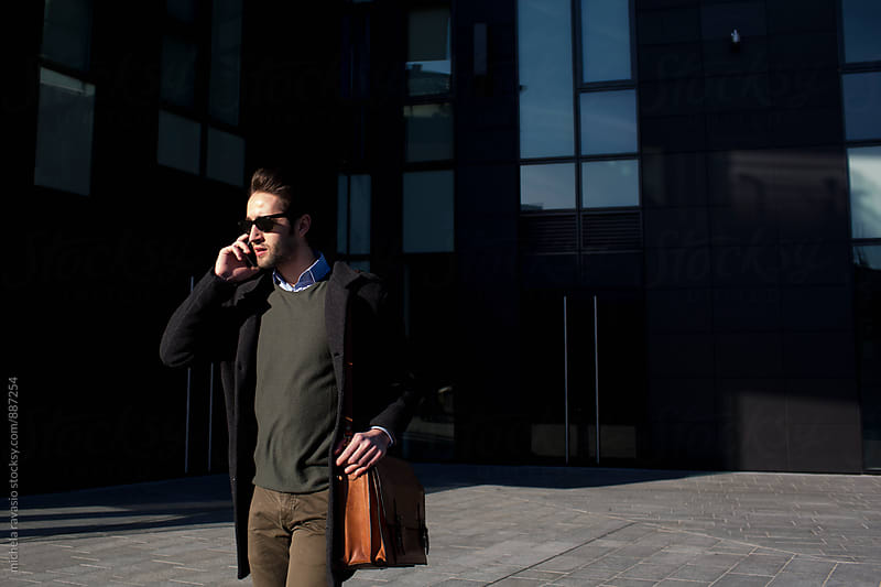 Young man talking on cell phone outdoors by michela ravasio for Stocksy United