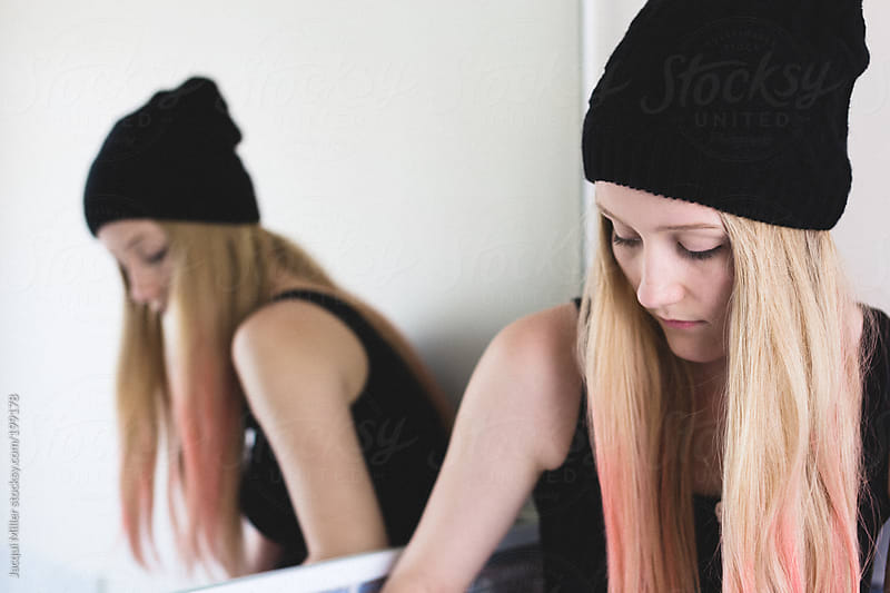 Teen girl, with pink dyed hair, sits on a bathroom sink. Her image is reflected in the mirror. by Jacqui Miller for Stocksy United