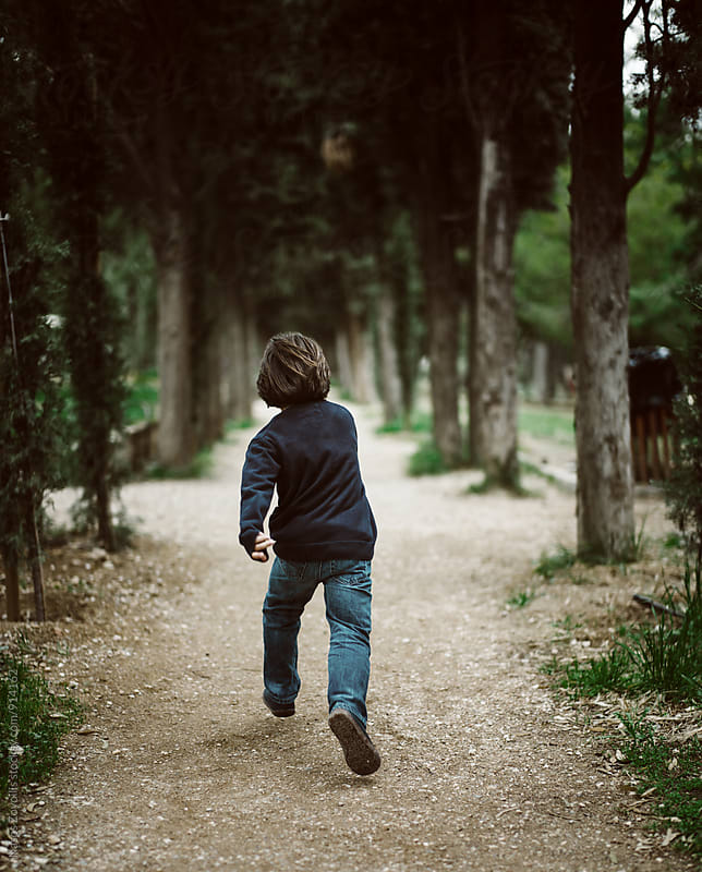 Small boy running in a forest by Nasos Zovoilis for Stocksy United