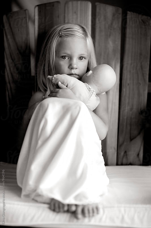 Little Girl In White Slip Dress Holding Baby Doll by Dina Giangregorio for Stocksy United