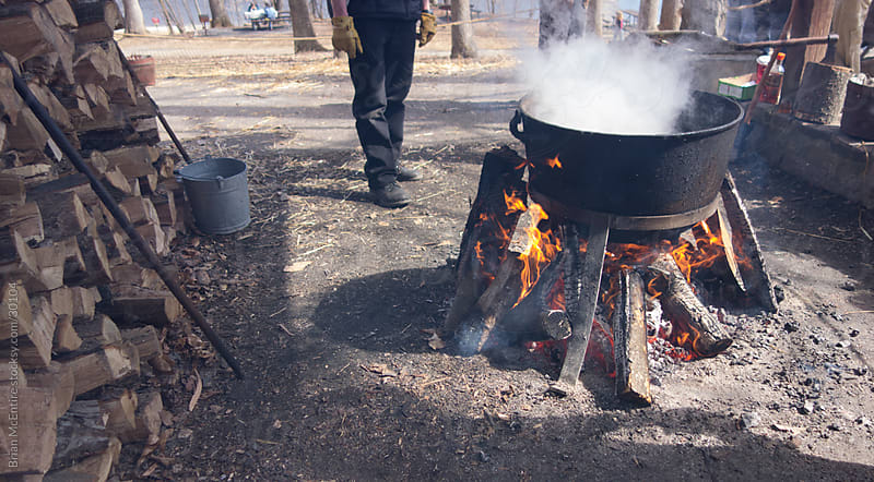 Making Maple Syrup: Reducing Sap in Boiling Cauldron Over Fire  by Brian McEntire for Stocksy United