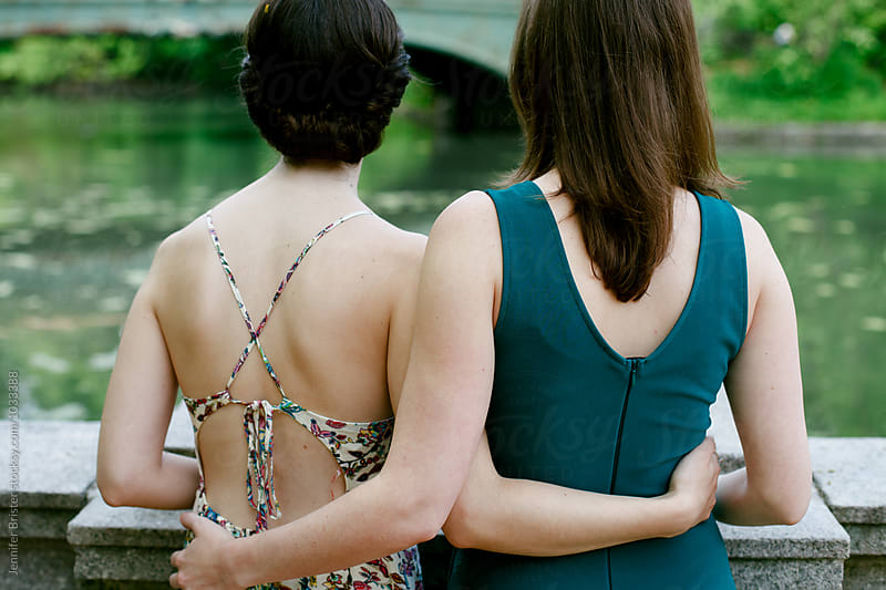 Two women holding each other and looking out at water by Jennifer Brister for Stocksy United