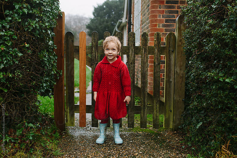 Little girl in a beautiful knitted red cardigan stands by a garden gate in the rain. by Julia Forsman for Stocksy United