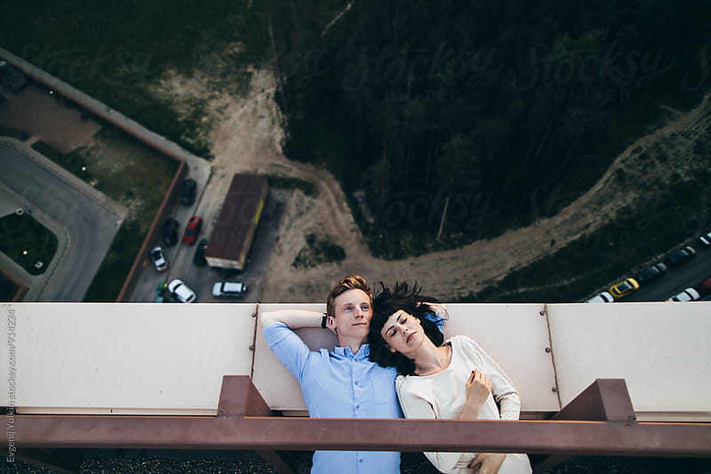 Young couple laying on the adge of the rooftop by Evgenij Yulkin for Stocksy United