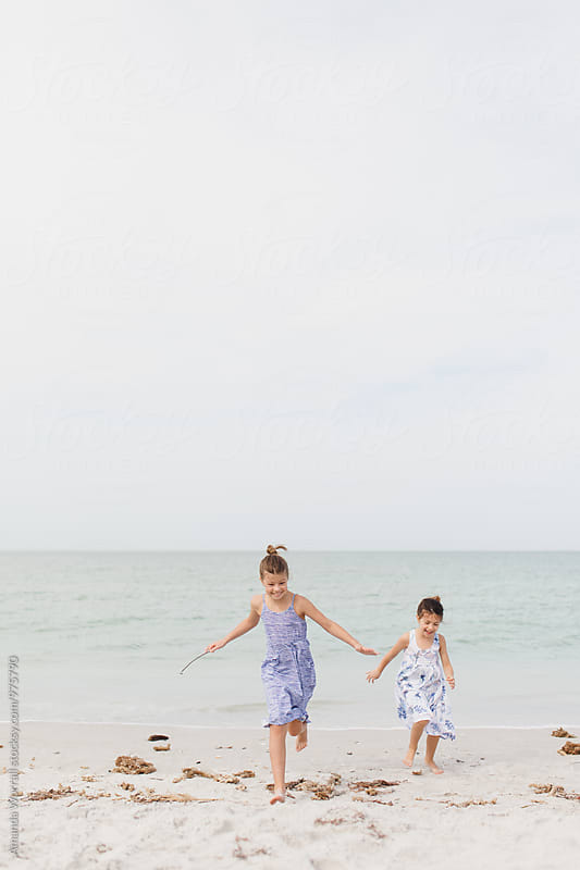 Two girls running toward the camera at the beach, laughing by Amanda Worrall for Stocksy United
