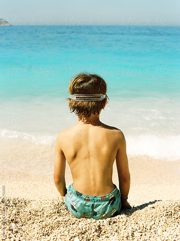Rear view of boy wearing goggles on a beach by Kirstin Mckee for Stocksy United