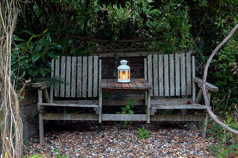 Weathered hidden bench at dusk with lamp by Paul Phillips for Stocksy United