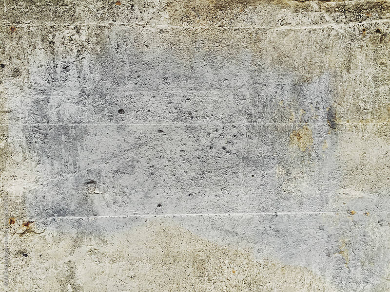 Grey paint covering graffiti tag on worn concrete wall by Paul Edmondson for Stocksy United