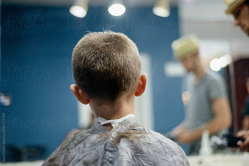 Boy gets his hair cut at a barber shop by Cara Dolan for Stocksy United