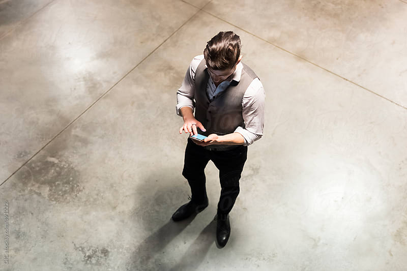 Businessman using a phone in the office by GIC for Stocksy United