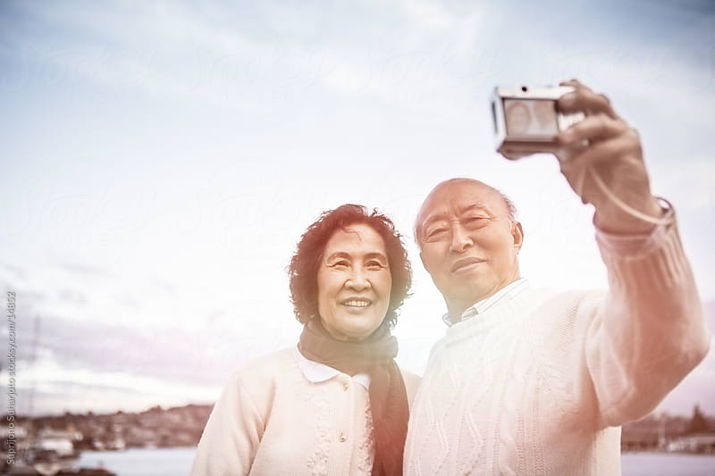 Traveling senior Asian couple posing and taking picture with a camera by Suprijono Suharjoto for Stocksy United