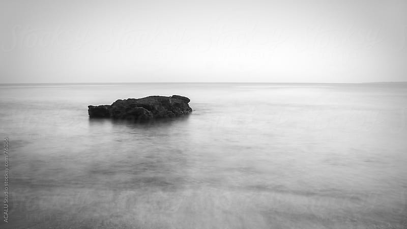 Minimalist seascape with rock at B&W by ACALU Studio for Stocksy United