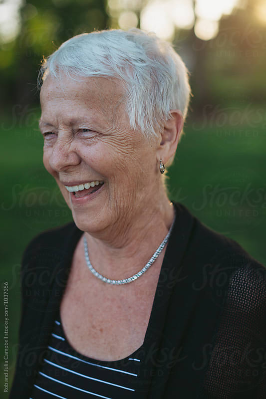 Happy caucasian senior woman smiling outside by Rob and Julia Campbell for Stocksy United