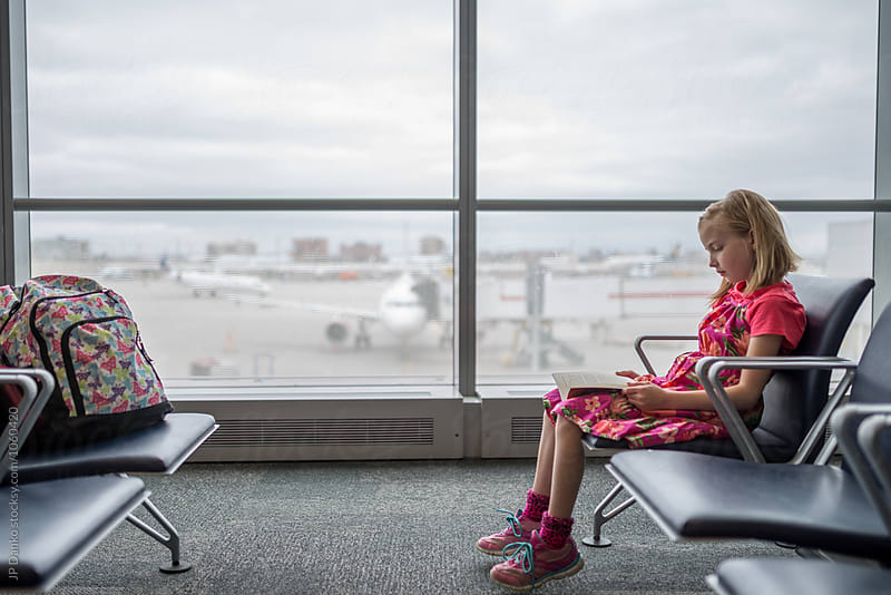 Little Girl Waiting For Flight at Modern Airport Traveller Lounge While Reading A Book by JP Danko for Stocksy United