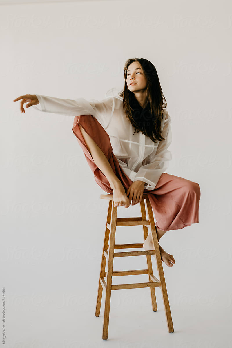 Woman Model Posing On A Stool In Culottes And A Raincoat By Mango Street Lab Woman Model Stocksy United