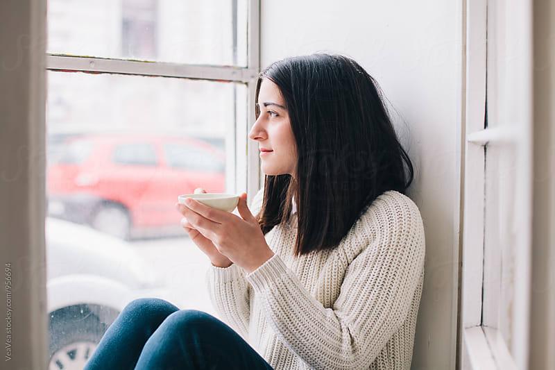 Brunette woman drinking tea sitting near a window by VeaVea for Stocksy United