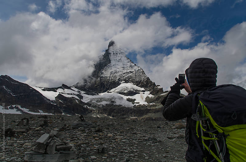 Hiker taking photo of the Matterhorn with phone by Neil Warburton for Stocksy United