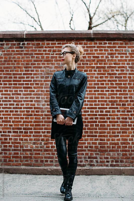 Stylish woman in black in the street holding digital tablet by michela ravasio for Stocksy United