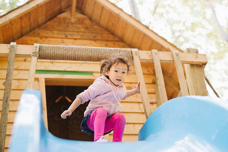 Toddler girl playing slides on playground by MaaHoo Studio for Stocksy United