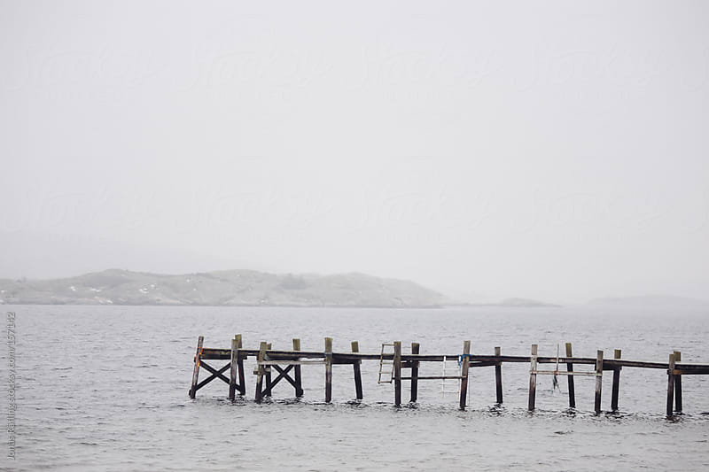 Jetty into foggy sea by Jonas Räfling for Stocksy United