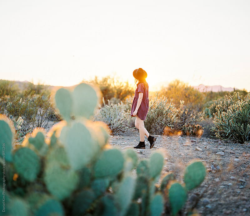 Young woman walking in desert by Daniel Kim Photography for Stocksy United