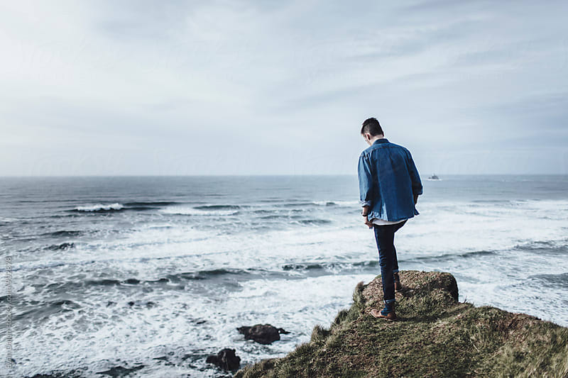 Young Man Standing on Cliff by the Ocean by Evan Dalen for Stocksy United