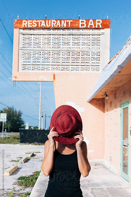 Woman in front of Abandoned Restaurant by Stephen Morris for Stocksy United