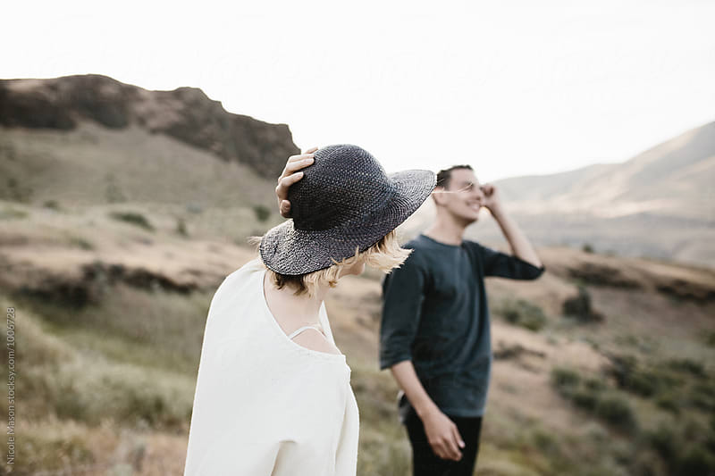young woman holding hat on head posing with man in desert by Nicole Mason for Stocksy United