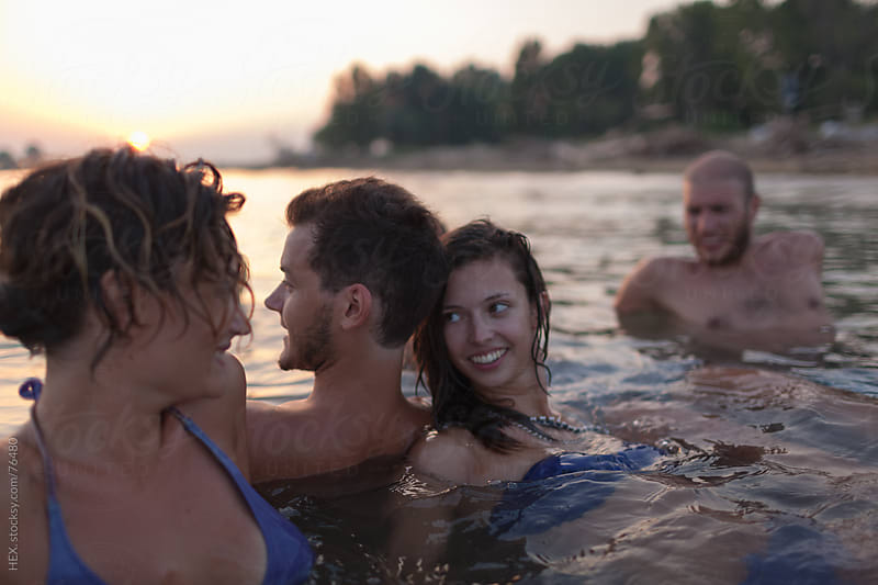 Friends Swimming During Sunset by HEX. for Stocksy United