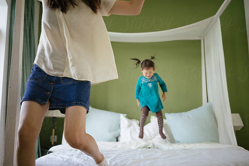 Cute toddler girl playing with her young mother on bed by MaaHoo Studio for Stocksy United