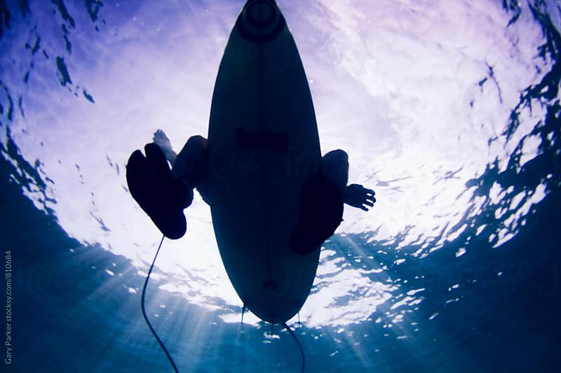 A surfer sitting on a board from underwater by Gary Parker for Stocksy United