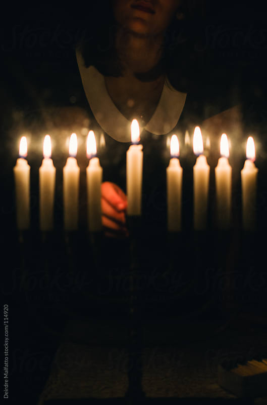 lighting candle in a menorah for Chanukah by Deirdre Malfatto for Stocksy United