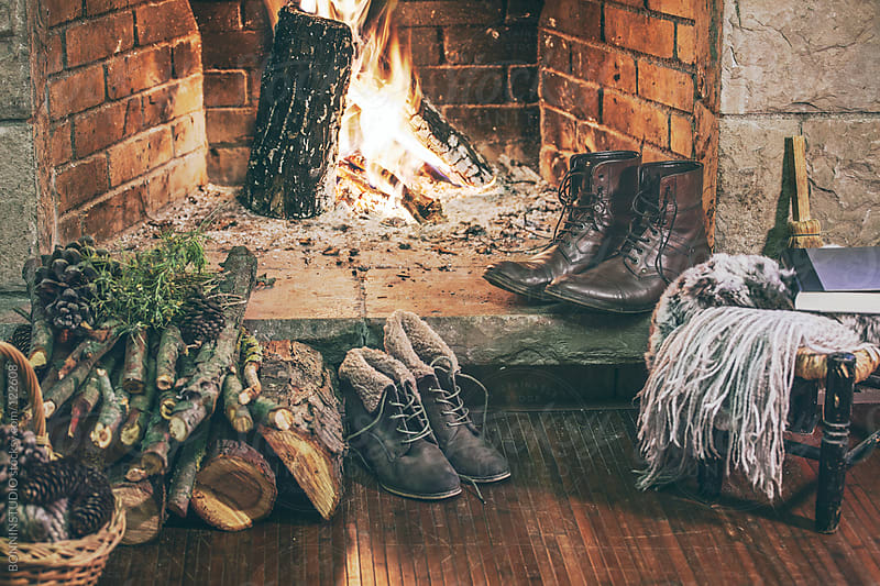 Winter boots in front a fireplace.  by BONNINSTUDIO for Stocksy United