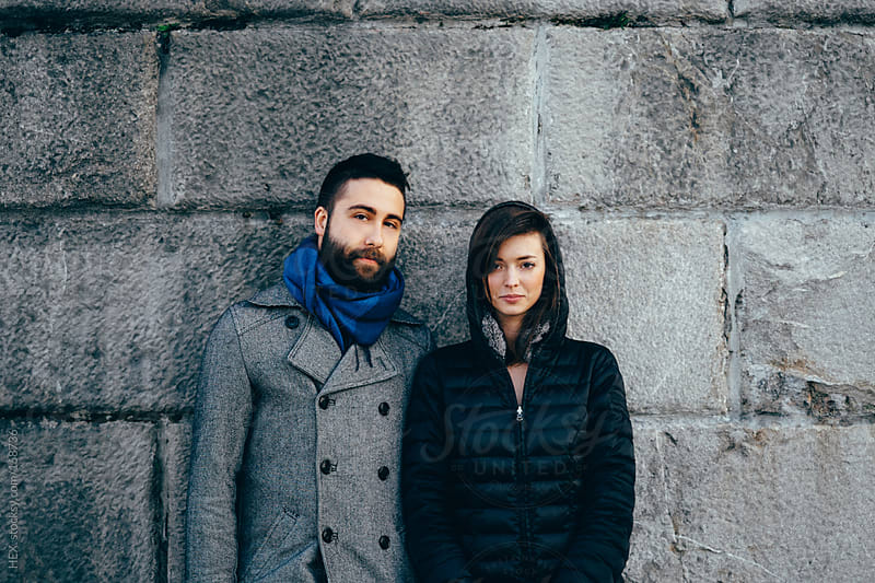 Young Couple Visit Portrait in front of a Grey Wall by HEX. for Stocksy United
