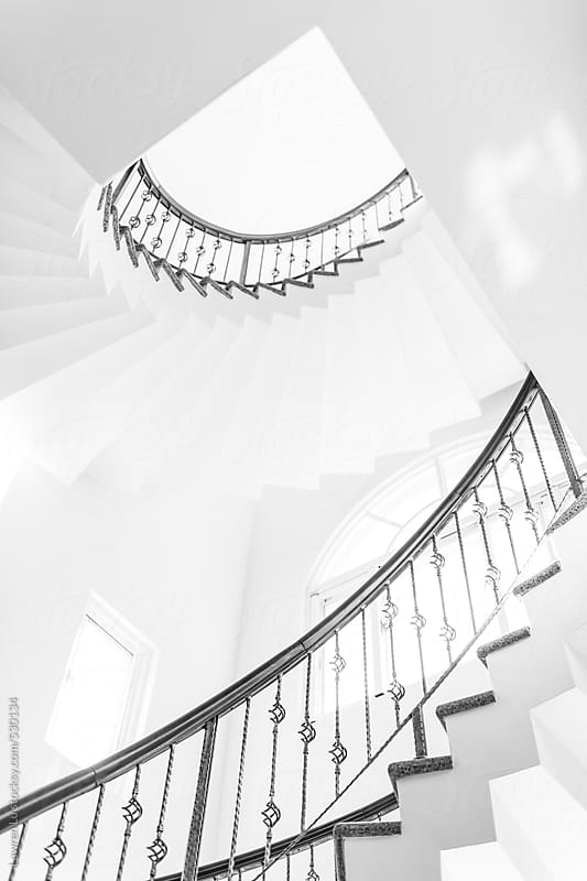 Bright white interior spiral staircase with iron balustrade passing sunny window in architectural by Lawren Lu for Stocksy United