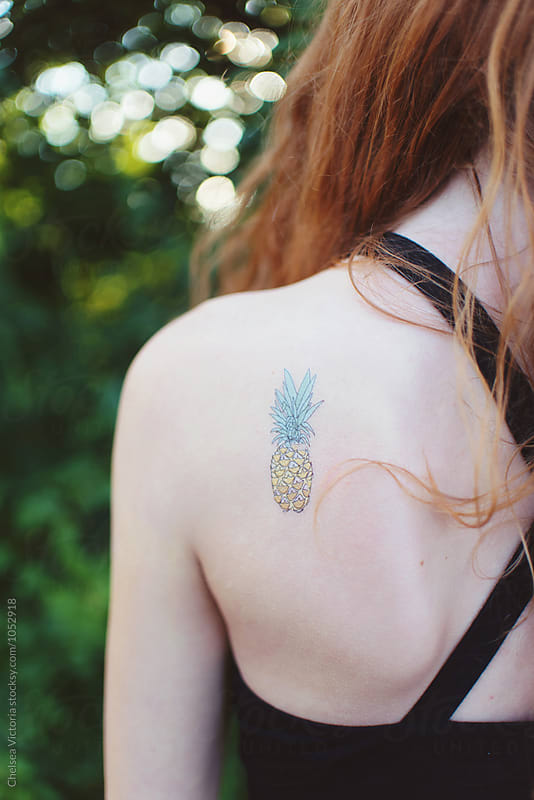 A teenage girl with a tattoo of a pineapple by Chelsea Victoria for Stocksy United
