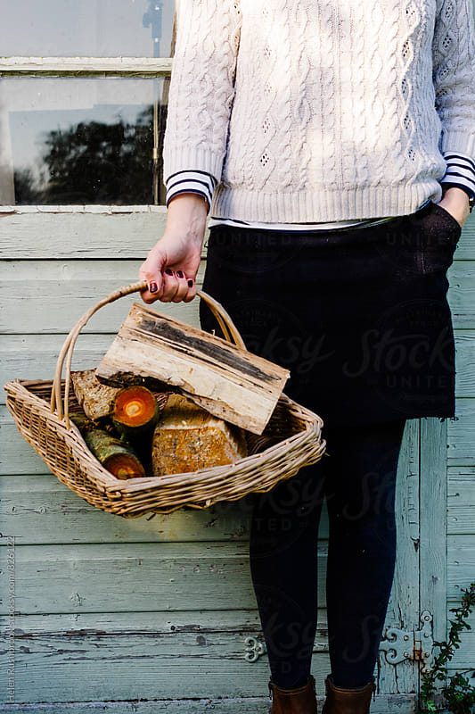 Woman holding a basket of firewood. by Helen Rushbrook for Stocksy United