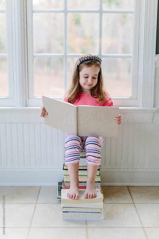 Cute young girl sitting on a stack of books reading by Jakob for Stocksy United
