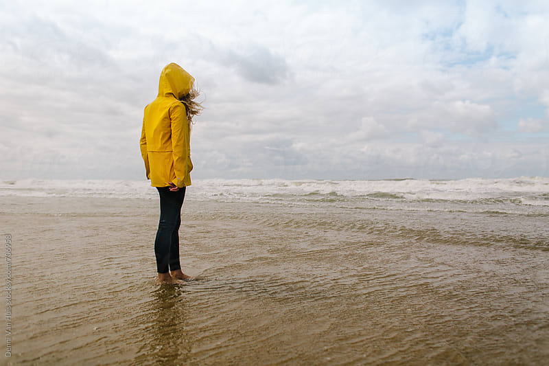 Woman standing in water on a windy beach wearing a yellow raincoat by Denni Van Huis for Stocksy United