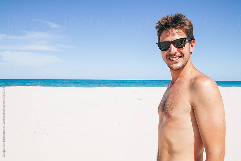 Young happy man portrait on white sand beach wearing sunglasses by Alejandro Moreno de Carlos for Stocksy United