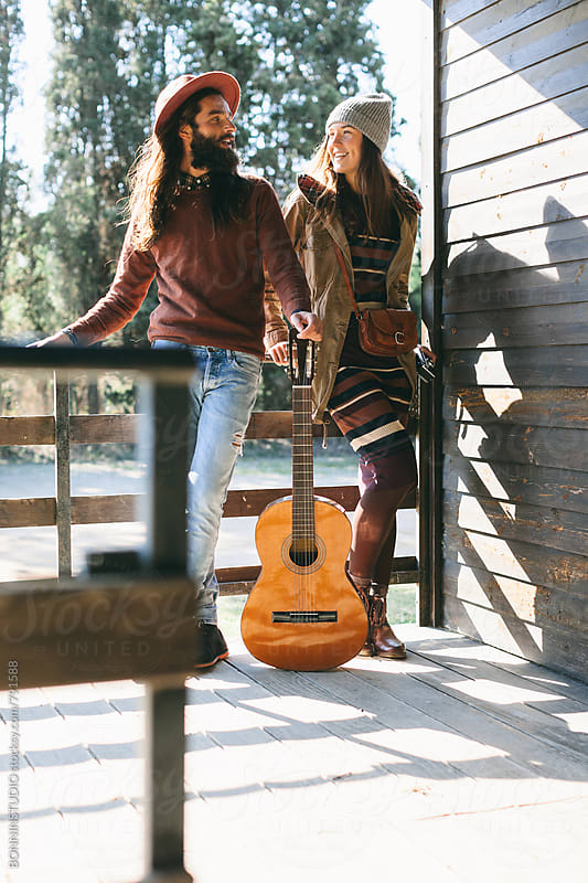 Hipster couple with a guitar enjoying day on a cabin porch. by BONNINSTUDIO for Stocksy United