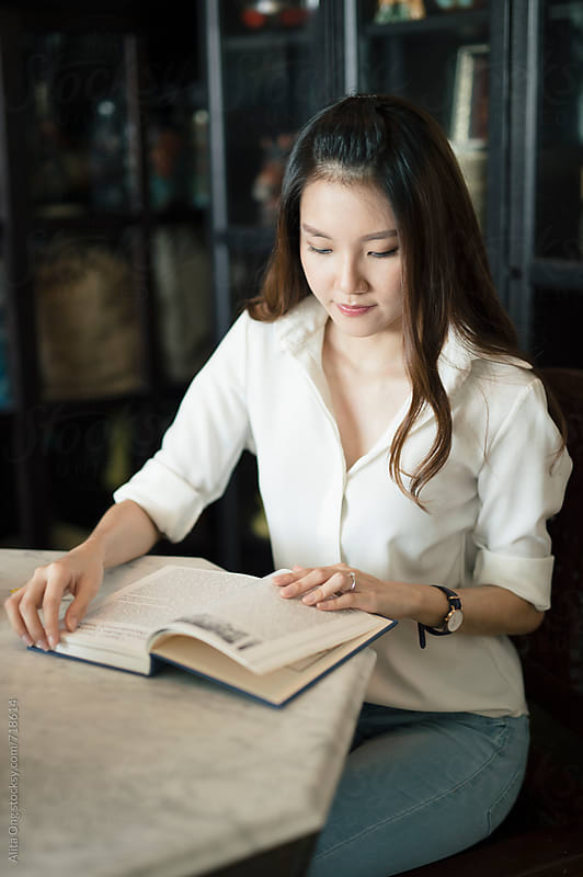 A woman reading a book by Alita Ong for Stocksy United
