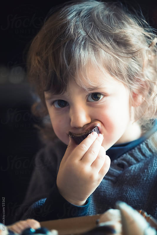 Little girl eating a chocolate pastry by Simone Becchetti for Stocksy United