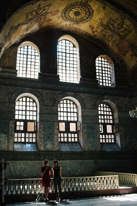 Two women discuss the architectural features of Hagia Sophia. by Julia Forsman for Stocksy United