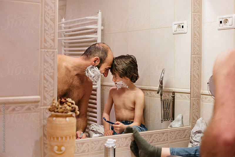 Man and six years old boy playfully looking at each other during shaving by Beatrix Boros for Stocksy United