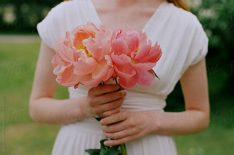 Woman holding peonies by Liubov Burakova for Stocksy United