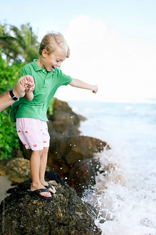 ocean splashes a happy boy by Kelly Knox for Stocksy United